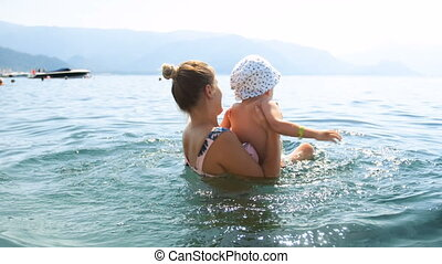 4k footage of young mother playing and lifting her toddler son in sea