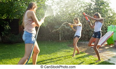 4k footage of young mother spraying water from garden hose over her daughter with toy guns