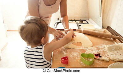 4k footage of young mother teaching her little son cutting dough for cookies with special plastic cutters