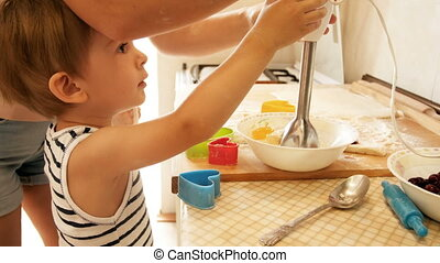 4k footage of young mother teaching her toddler son cooking and using electric blender on kitchen