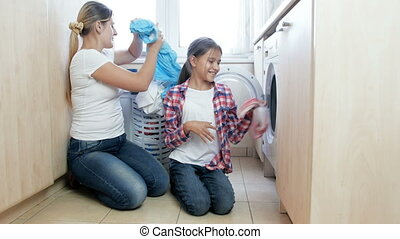 4k footage of young mother with teenage girl loading washing machine with dirty clothes at laundry