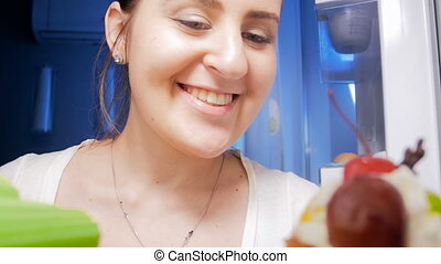 4k footage of young smiling woman looking inside of refrigerator at night and taking out celery