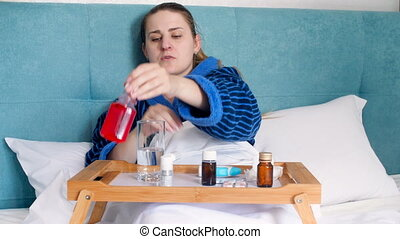4k footage of young woman feeling sick lying in bed and using lots of medicaments. Woman applying throat and nasal spray