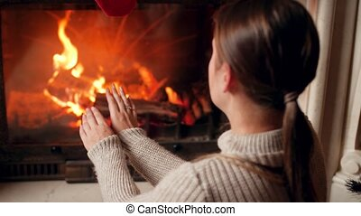 4k footage of young woman in sweater warming and rubbing her hands at burning fireplace in house