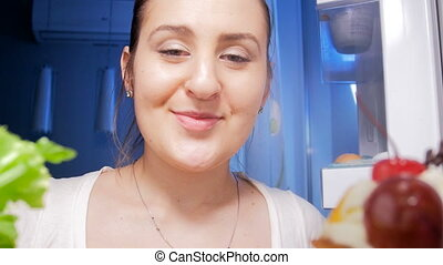 4k footage of young woman looking inside of refrigerator at house and taking celery
