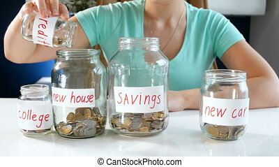 4k footage of young woman pouring money from on jar to other...