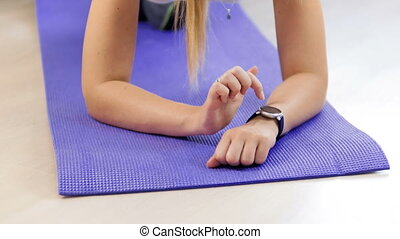 4k footage of young woman pressing touchscreen on smart watch before training on fitness mat