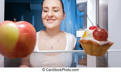 4k footage of young woman taking fresh apple from fridge at kitchen