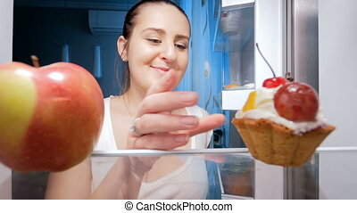 4k footage of young woman taking sweet cake from fridge at...
