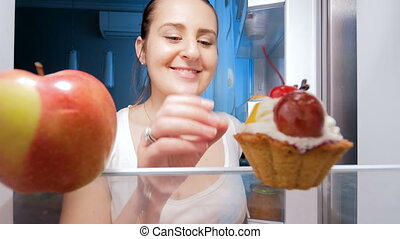 4k footage of young woman taking sweet cake from refrigerator at night