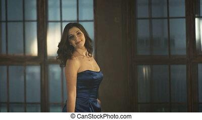4k Girl in a luxurious evening blue dress spinning around,...