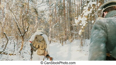 4K Group Of Re-enactors Dressed As German Wehrmacht Infantry Soldiers In World War II Running With Weapons In Winter Forest. Historical Re-enactment In Winter Snowy Forest