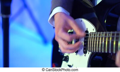 4k guitarist plays acoustic guitar on night club stage, flashes of colour lights