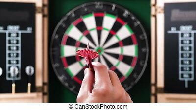 4K - Hand throws a dart into dartboard