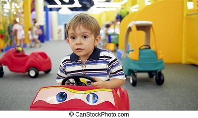 4k handheld video of little boy riding in pedal children car...