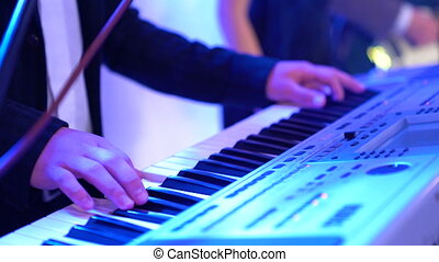 4k Male hands playing electric piano under colorful stage lighting, close-up