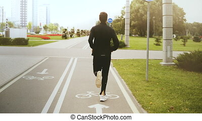 4K Man running along a city park road. Back view. Fitness...