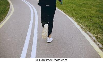 4K Man runs along an autumn park road. Back view. Sportsman...