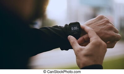 4K Man sets smart watch timer, runs out of focus. Athlete starts a smart watch tracker clock before jogging in the city.