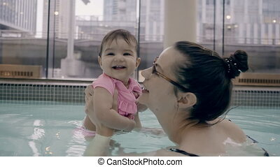 4K Mother and baby girl playing in a pool.