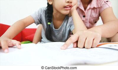 4K Mother teaching homework to Asian little girl at home for...