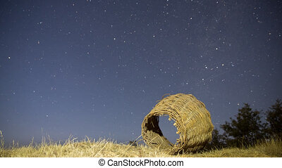 4K Night Time Lapse of stars and illuminated rusty wicker...