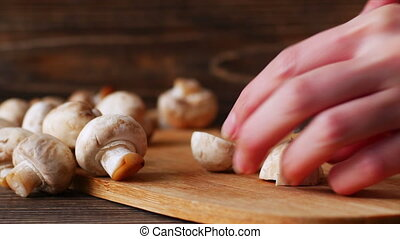 4k of woman hands cutting mushrooms in the kitchen