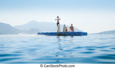 4k out of focus video of teenagers jumping from pontoon at...
