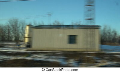 4K Point of view from the window of a passenger train. The deserted winter forest moves outside the window
