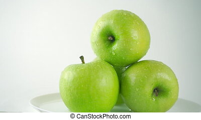 4K ProRes left to right dolly video of water being poured over green apples, light background