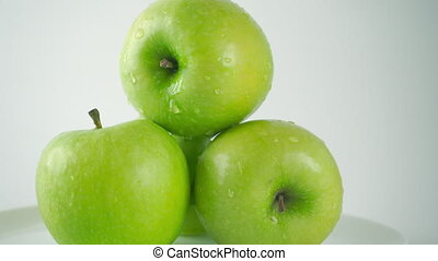 4K ProRes right to left dolly video of water being poured over green apples, light background