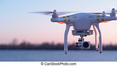 4K - Quadcopter flies near the camera. Drone close-up