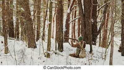 4K Re-enactor Dressed As American Soldier Of USA Infantry Of World War II Shooting From Rifle In Winter Forest. Historical Re-enactment.