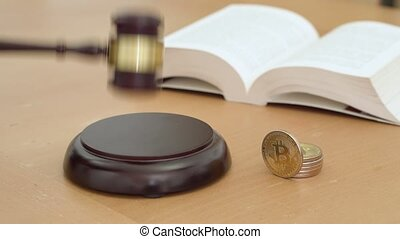 Bitcoin on table with book behind it, gavel striking on sound block, crypto currency legalization