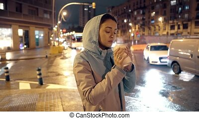 4k shot of a girl with takeaway coffee in the night city -...