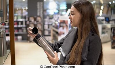 oung beautiful woman choosing thermos bottle in a store...