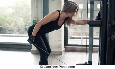 shot of Young fit woman doing triceps exercise using training machine in gym