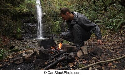 4k, slow motion. a male tourist fires a bonfire for a grill in the forest against the backdrop of a waterfall.
