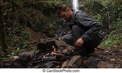 4k, slow motion. a male tourist fires a bonfire for a grill...