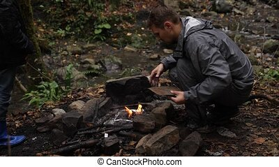 4k, slow motion. a man-tourist shoots a fire for a grill in...