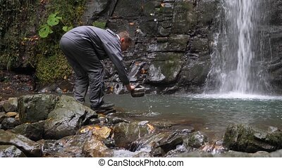 4k, slow motion. a tourist man is picking up water from a...