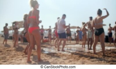 4k slow motion blurred video of people dancing on the beach...