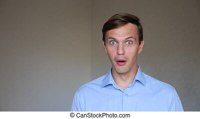 4k. Slow motion. Close up portrait of a young man. body language and gestures. he is surprised and confused