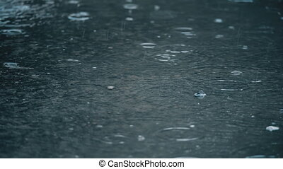 4K slow motion establishing shot of rain falling on pavement.