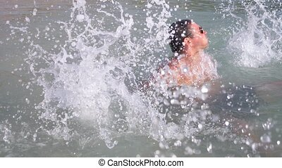 4k, slow-motion shooting, a young man dives into the sea in sunglasses. emerges