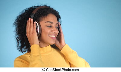 4K Smiling fashion model with headphones posing and dancing against blue background in studio. Beautiful young mixed race african female model enjoying music