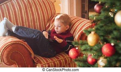 4k, sofa, vidéo, avoir, peu, utilisation, tablette, salle, garçon, mensonge, fetes, celebrations., hiver, vivant, amusement, enfant, computer.