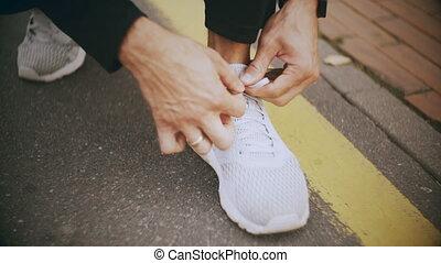 4K Sportsman tying shoelaces, preparing to start. Camera...