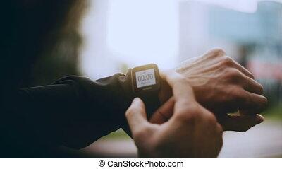 4K Sportsman using smart watch timer before start. Man...