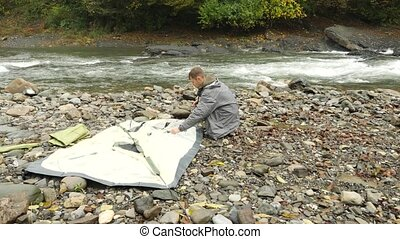 4k. the guy puts a tourist tent on the shore of a mountain river.